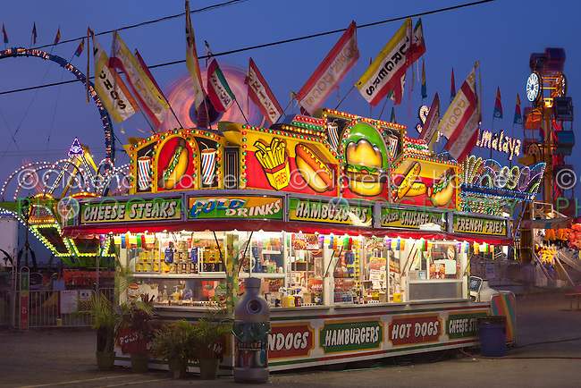 A food concession selling various snacks at the New Jersey State Fair, Sussex County Fairgrounds, Augusta, New Jersey, with midway rides in the background.