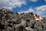 Group of backpackers climb the active Cerro Negro volcano, holding wooden boards and carrying orange protective suits, Nicaragua