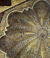 Dome above the maqsura, a richly decorated ribbed vault with small dome in front of the mihrab, redecorated under Al-Hakam II in 961, in the Cathedral-Great Mosque of Cordoba, in Cordoba, Andalusia, Southern Spain. The ceiling is decorated with kufic script, floral motifs, and a sunburst radiating from a tiny central star, with light coming from 8 latticed side windows. The first church built here by the Visigoths in the 7th century was split in half by the Moors, becoming half church, half mosque. In 784, the Great Mosque of Cordoba was begun in its place and developed over 200 years, but in 1236 it was converted into a catholic church, with a Renaissance cathedral nave built in the 16th century. The historic centre of Cordoba is listed as a UNESCO World Heritage Site. Picture by Manuel Cohen