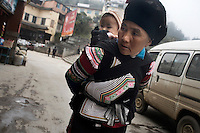 An ethnic minority Hani woman carries a baby along a street in Xinjie, Yuanyang County, Yunnan Province, China.