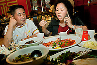 Qin Lingzhi, the founder and owner of The West Lake Restaurant, talks on a mobile phone while eating a meal with the head chef Gong Nanxi. Able to seat up to 5,000 people at one sitting, The West Lake Restaurant is the biggest Chinese restaurant in the world. Each week its diners, who staff are taught are 'the bringers of good fortune', devour 700 chickens, 200 snakes, 1,200 kgs of pork and 1,000 kgs of chillis. Its 300 chefs cook in five kitchens and its staff total more than 1,000.It is fully booked most nights.