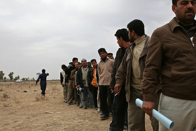 Men line up to apply for jobs as police officers in Kirkuk, Iraq. Iraqi officials had sought to fill 1,300 slots for the next training class, but were overwhelmed when more than 4,000 applicants showed up on the first day of a five-day recruiting drive. More than half were turned away at the gate, and hundreds of others waited in line for hours, but never got a chance to submit their papers. The event was shut down after a U.S. advisor observed an Iraqi recruiting officer take a bribe from an applicant. Dec. 6, 2007. DREW BROWN/STARS AND STRIPES