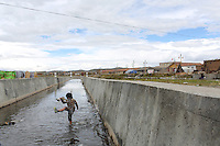 A young boy plays in a water channel in the town of Sershul, in northern Sichuan Province on the Tibetan Plateau. The region is known as Sanjiangyuan, or Three Rivers Headwaters, as it is the source of the Yangtze, Mekong and Yellow Rivers which feed millions of people who live downstream.