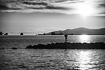 A silhouetted man standing on a jetty staring into the sunset with expressive gesture.