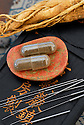Herbal capsule, Ginseng root, and acupuncture needles.
