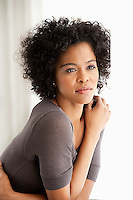 Young African American woman leaning against window
