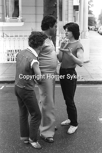 Arabs London UK 1977. Middle Eastern people came to Britain for subsidised health care in Harley Street clinics. Two rent boys talking to Arab male health tourist Earls Court.