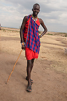 This man is a junior elder in the Amboseli Maasai tribe.  As soon as a warrior gets a wife, their long hair is shaved off.  They also carry a  stick and not a spear as a symbol of wisdom upon joining the next rank in the life of a Masai- elderhood.