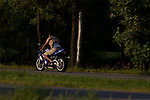 A man rides a metalic blue motorcyle also called a &quot;crotch rocket&quot; down a highway in Minnesota