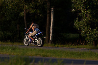 "A man rides a metalic blue motorcyle also called a ""crotch rocket"" down a highway in Minnesota"