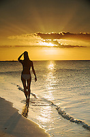 female silhouette in a bikini on the beach at sunset