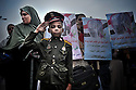 Young boy wearing a military costume in a protest against military government in Tharir square. Thousands of Islamist and secular protesters gathered in Cairo's Tahrir Square today for a mass rally to press the ruling military to hand over power to a civilian government.