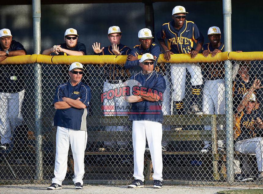 Boca Ciega Pirates coaches and players, including Desmond Mack (14), Chris Riley (13) and Anquante Allen (31), watch the action from the dugout during a game against the Lakeland Spartans at Boca Ciega High School on March 2, 2016 in St. Petersburg, Florida.  Boca Ciega defeated Lakewood 2-1.  (Mike Janes/Four Seam Images)