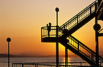 Summer time fun along Seattle waterfront with Puget Sound and mother and daughter silhouetted at sunset Seattle Washington State USA