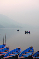Row boats line the shore of Phewa lake in Pokhara, Nepal. Pokhara is situated in the northwestern corner of the Pokhara Valley and is the gateway to the Annapurna mountain range. The modern tourist hub once sat along an important trading route between China and India.
