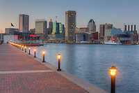 The sky begins to darken over the skyline of Baltimore, Maryland as sunset approaches.