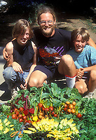 Father and children with vegetable harvest, beets, squash, teaching kids to love gardening