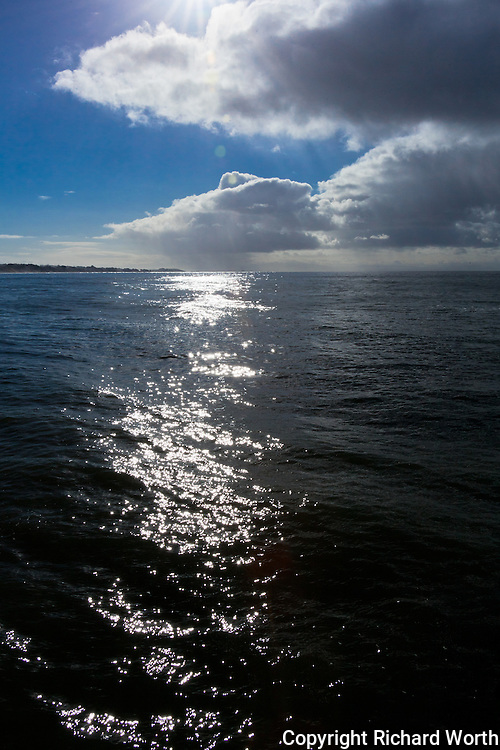 The morning sun peeks through clouds, dappling the ocean with glitter at Seacliff State Beach.