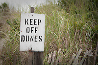 """A """"keep of dunes"""" sign is pictured by the beach in Ocean Beach on Fire Island in New York state, Wednesday August 3, 2011. The incorporated villages of Ocean Beach and Saltaire within Fire Island National Seashore are car-free during the summer tourist season and permit only pedestrian and bicycle traffic."""