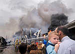 04/09/08-(Harrisonburg).Daniel Fisher holds his son, 22-month-old Andrew, as he watches firefighers battle a blaze at Dave's Recycling on South High Street Wednesday afternoon. Fisher is a co-owner of the business with his father and brothers..(Pete Marovich/Daily News-Record)