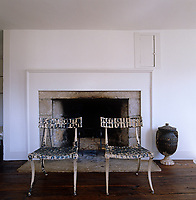 A pair of painted ironwork chairs with latticed seats have been placed infront of a stone fireplace