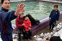 Tourists pose with a seal as zookeepers stand nearby at the Hefei Zoo in Hefei, China.