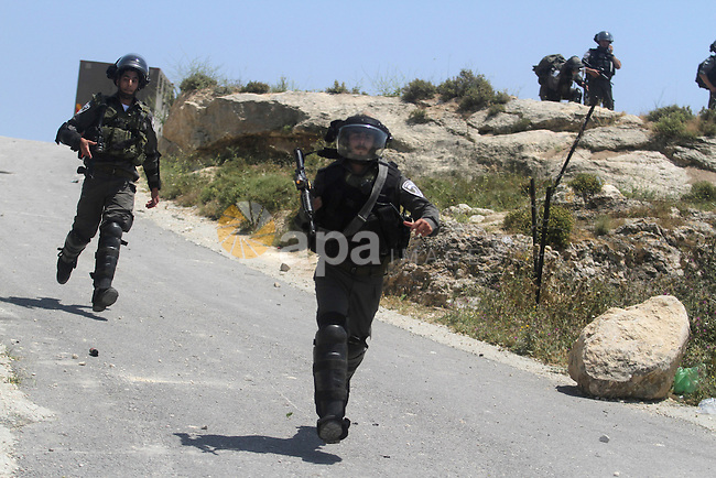 Israeli border police take position during clashes between Palestinian villagers from Oref and Jewish settlers after Israeli settlers attacked villages near Nablus City 30 April 2013. Reports state that the clashes occured after an Israeli settler was stabbed to death by a Palestinian man. Israeli media reported that the Palestinian attacker took the settlers' weapon and began firing at a nearby Israeli border guard force, who returned fire, wounding the attacker. Photo by Issam Rimawi