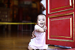 A smiling child props herself up inside a doorway of the Mieu Temple in the Citadel in Hue, Vietnam. Built in 1821, the temple honors the emperors of the Nguyen Dynasty, the last of whom abdicated in 1945, as Vietnam sought independence from the French. The temple was one of those least damaged by heavy fighting during the Tet Offensive of 1968, at the height of the Vietnam War. April 21, 2013. Photo by Le Thi Van Ha.