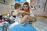 Amani El Assar, a nurse and patient educator, places a child on a scale in a clinic in Shejaiya, a neighborhood of Gaza City that was hard hit by the Israeli military during the 2014 war. The clinic is run by the Department of Service for Palestinian Refugees of the Near East Council of Churches, a member of the ACT Alliance, and funded in part by the Pontifical Mission for Palestine.  This clinic has twice been destroyed by Israeli air strikes, but each time has been rebuilt by DSPR.
