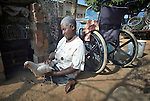 Edith Ncube had polio as a child and today uses a wheelchair. Here she handles one of the chickens she raises in the yard of her house in Bulawayo, Zimbabwe. Her wheelchair was provided by the Jairos Jiri Association with support from CBM-US.