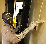 Lagul Dennis paints his tiny bedroom in his brother&amp;#xD;'s home in Naguru Estates,  in Kampala, Uganda, November 5, 2003. Residents say that the city had long since stopped maintaining the homes leaving the residents to pay for maintennance and repairs from their own pocket. Residents were given six months to vacate the houses by the city which  planed to build a satelight neighborhood. This same piece of land also was recently advertised for sale for an auto dealership. Public outrage quashed the plan to evict the residents from the low-income housing.(Rick D'Elia)<br />