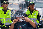A young man smokes marijuana in front of Colombian policemen on a street during celebrations of the International Day of the Marijuana and for the legalization in Medellin, Colombia, May 5, 2012. Photo by Fredy Amariles/VIEWpress.