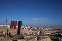 Laundry hangs from the Abu Nowar Bedouin community with Ma'aleh Adumim settlement in background.  Already served demolition orders, the 118-person community bides time, squeezed between Ma'aleh Adumim on one side and a military base on the other.
