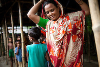 A widow, Rubi Begum, 40, adjusts her sari while working as a saleswoman in Ghagoa Villlage, Gobindagonj Upazila, Gaibandha, Bangladesh on 19th September 2011. Living alone after her husband's passing, she has now (since 2.5 years) found financial independence by working as a saleswoman, earning 3500 - 5000 Bangladeshi Taka per month. She is one of many rural Bangladeshi women trained by NGO CARE Bangladesh as part of their project on empowering women in this traditionally patriarchal society. Named 'Aparajitas', which means 'women who never accept defeat', these women are trained to sell products in their villages and others around them from door-to-door, bringing global products from brands such as BATA, Unilever and GDFL to the most remote of villages, and bringing social and financial empowerment to themselves.  Photo by Suzanne Lee for The Guardian