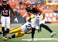 Tyler Eifert #85 of the Cincinnati Bengals runs through a tackle by Mike Mitchell #23 of the Pittsburgh Steelers after catching a pass during the game at Paul Brown Stadium on December 12, 2015 in Cincinnati, Ohio. (Photo by Jared Wickerham/DKPittsburghSports)
