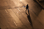 Crossing a mostly abandoned street in Chicago's Loop, a man heads for home on a late night in the city.