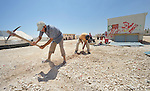 Men dig a foundation for a new modular home in the Zaatari refugee camp near Mafraq, Jordan. Established in 2012 as Syrian refugees poured across the border, the camp held more than 80,000 refugees by 2015, and was rapidly evolving into a permanent settlement. Tents for many families have been replaced with modular houses, or caravans. The ACT Alliance provides a variety of services to refugees living in the camp.