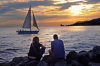Youg couple watching a sailing boat at sunset on Lac Leman (lake Geneva) - Montraux Switzerland