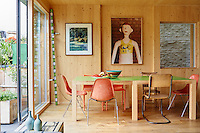The artist Richard Woods has built a timber house where he can both create and showcase his bold, bright work. The scent of timber pervades the interior with floors of solid oak and walls constructed from cross laminated timber panels. The dining table with a bright green top was made by Woods. Contrast is provided by an assortment of dining chairs.