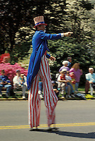 Americana Stilt walking Uncle Sam reenactor  marches  in small town holiday celebration parade.