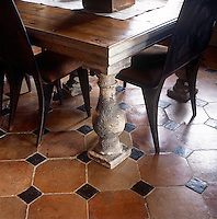 A detail of a dining room with a terracotta tiled floor. The room has a wooden table with stone legs and wooden dining chairs.