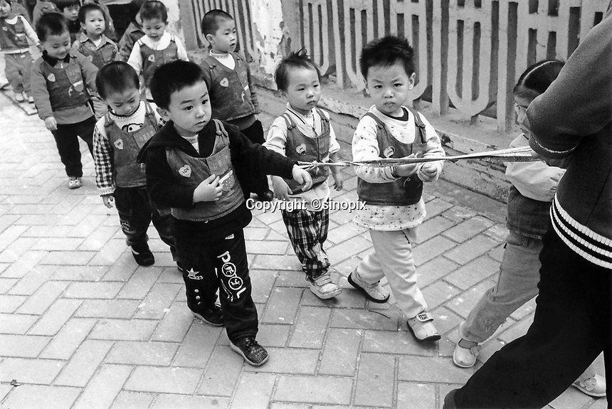 School children being tied up on the way to school, to avoid being stolen in Guangzhou, China. Kidnapping of young children especially boys are in the thousands as parents without a son are willing to pay large ammounts for a son.<br /> Jul 2004<br /> <br /> photo by Richard Jones / Sinopix