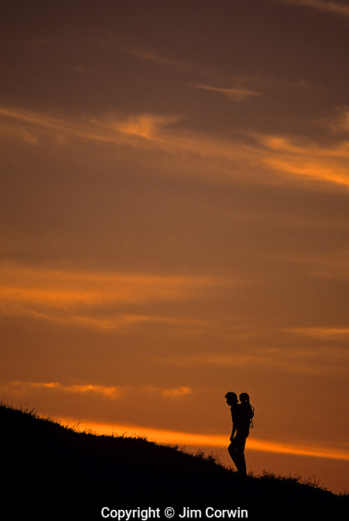 Silhouetted man with child carrier hiking up hill at sunset