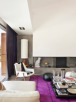 A 1950's French black and white armchair, contemporary coffee table and pair of Moroccan leather poufs on a purple Pamplona rug by Carpet Diem in front of the polished concrete fireplace