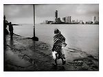 Muslim woman walks out isthmus, which is covered at high tide, to the Haji Ali Dargah Mosque while new apartment blocks of Mumbai's elite rise in the Worli district of Mumbai, India.