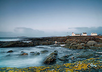 Sunset at Tungenes lighthouse at winter with crashing waves.