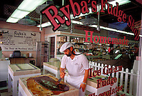 AN EMPLOYEE OF RYBA'S FUDGE SHOP ON MACKINAC ISLAND, MICHIGAN COOLS FUDGE ON A MARBLE SLAB FOR CUSTOMERS TO SEE.