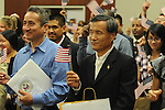 Braulio Ramon (left) and Shengkun Wen wave U.S. flags after becoming United States citizens during a naturalization ceremony in federal court in Oxford, Miss. on Friday, June 29, 2012. Forty seven persons took the oath of citizenship.