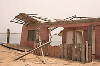 Ghana - Kpogbor Island - A house destroyed by the rising sea level as a repercussion of the sea wall that was destroyed along the village located at the West.