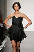 Model walks runway in a black lace pencil skirt dress, strapless mikado organza bodice, sweetheart neckline, mikado organza peplum skirt with tie at natural waist bridesmaid dress by Lazaro Perez, from the Noir by Lazaro Spring 2012 Bridal fashion show.